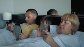 A happy family with one child lying on the bed and using a digital tablet and smartphones. Modern technologies of. Virtual life. The concept of lifestyle stock footage