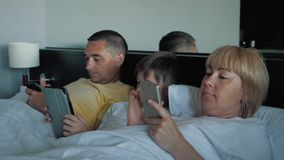 A happy family with one child lying on the bed and using a digital tablet and smartphones. Modern technologies of. Virtual life. The concept of lifestyle stock video footage