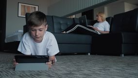 A happy family with one child lying on the carpet and using a digital tablet and smartphones. Modern technologies of. Virtual life. The concept of lifestyle stock video