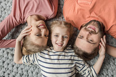 Happy family with one child lying together on grey knitted carpet. Top view of happy family with one child lying together on grey knitted carpet Royalty Free Stock Photo