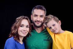 Happy family with one child. Portrait of happy family with one child looking at camera on black royalty free stock photo