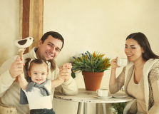 Happy family with one year old baby girl drinking coffee indoor Royalty Free Stock Images
