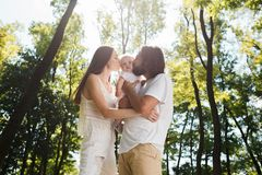 Happy family on the open air. Young dark-haired woman and her husband are kissing their charming little daughter. stock image