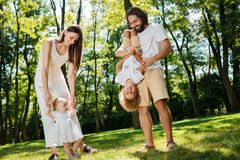 Happy family on the open air. Young dark-haired woman walking with her little daughter and her husband playing with son. royalty free stock images