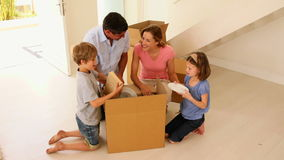Happy family opening box in their new home stock footage