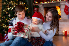 Happy family opening Christmas gift sitting in living room Stock Images