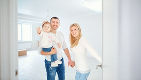 A happy family opens the door to their apartment. Housewarming Royalty Free Stock Photos