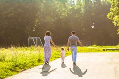 Happy family outdoor activity. Rear view of parents and baby daughter having fun and walking in summer park. Happy family outdoor activity. Rear view of parents stock photography