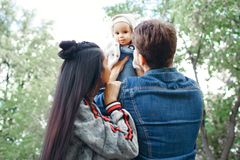 Happy family outdoors activity, father raises baby up, laughing and playing, father shows mother how to throws baby with safety royalty free stock photo