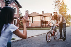 Happy family outdoors. Dad is teaching daughter how to ride bicycle. Mother is taking photo on a smart phone stock photos