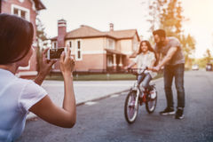Happy family outdoors. Dad is teaching daughter how to ride bicycle. Mother is taking photo on a smart phone stock image