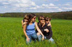 Happy family outdoors on green field Stock Photography