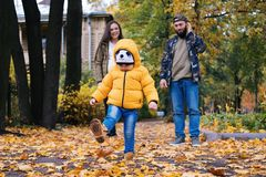 Happy family outdoors. Mother, father and baby on autumn walk in the park royalty free stock photo