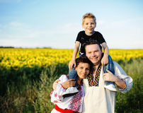 Happy family outdoors. Happy mother, father and son on the field with sunflowers Royalty Free Stock Photo