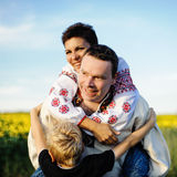 Happy family outdoors. Happy mother, father and son on the field with sunflowers Stock Images