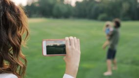 Happy family outdoors. Mother shooting video on the smartphone. Father and little daughter hugging and having fun stock video footage