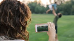 Happy family outdoors. Mother shooting video on the smartphone. Father and little daughter hugging and having fun stock footage