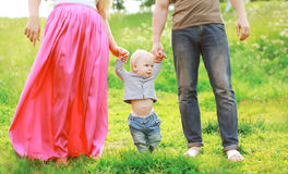 Happy family outdoors! Parents and baby on the grass. In sunny summer day Royalty Free Stock Photo
