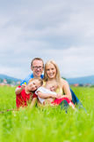 Happy Family outdoors sitting on grass Royalty Free Stock Photo