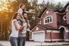 Happy family outdoors. Happy family is standing near their modern house and smiling stock photo