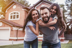 Happy family outdoors. Happy family is standing near their modern house, smiling and looking at camera