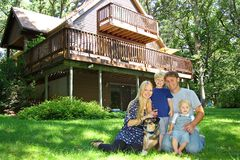Happy Family Outside by Cabin. A young, attractive, happy family of four; mother, father, baby, and young child, is sitting outside with their dog in front of a Stock Images
