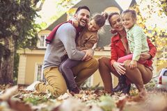 Happy family outside in colorful fall backyard poses to camera.