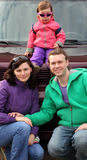 Happy family in outwear near car Stock Image