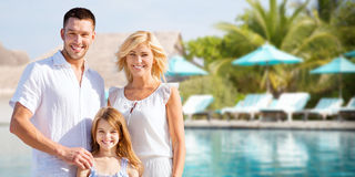 Happy family over hotel resort swimming pool. Summer holidays, travel, tourism, vacation and people concept - happy family over hotel resort swimming pool and Stock Images