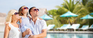 Happy family over hotel resort swimming pool. Summer holidays, travel, tourism, vacation and people concept - happy family over hotel resort swimming pool and Royalty Free Stock Photos