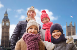 Happy family over london city background. Family, travel, tourism, winter holidays and people concept - happy parents with kids over london city background Stock Image