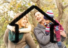 Happy family overlaid with house shape in park Stock Photos