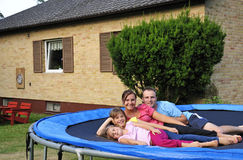 Happy family with own villa. Family portrait on garden trampoline with own villa background Royalty Free Stock Image