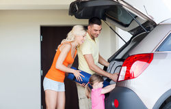 Happy family packing things to car at home parking Stock Photos