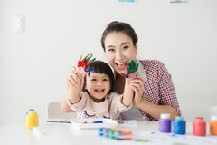 A happy family is painting. Mom help her daughter drawing royalty free stock photography