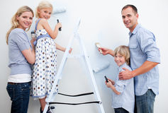 Happy family painting a room with brushes Stock Photo