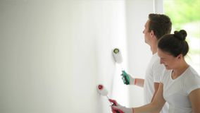 Happy family paints the wall with white paint. Repair in the apartment concept. stock footage