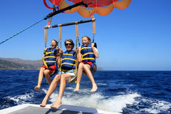 Happy Family Parasailing. Father and Twin Daughters Joyfully Para-sailing Against a Blue Summer Sky Stock Images