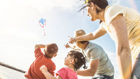 Happy family with parents and children playing together with kite. At beach vacation - Summer joy happiness concept with mixed race people having candid genuine Stock Photos