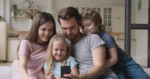 Happy parents with children having fun using smartphone at home