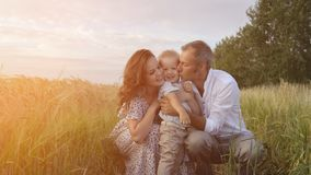 Family walking on meadow, parents playing with son. Happy family, parents hugs their little son. Mother, father and child leisures together outdoor. Mom, dad and royalty free stock photos