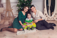 Happy family parents and kid with gifts near the Christmas tree. Royalty Free Stock Photo
