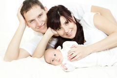 Happy family, parents with lying newborn baby
