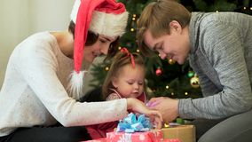 Happy family, parents showing Ney Year decorations to their cute child in front of Christmas tree. Mother in Santa hat royalty free stock photos