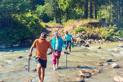 Happy family - parents and teenage son walk across mountain rive. R barefoot on a sunny day. Awesome travel in wilderness with family Stock Image