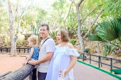 Happy family - parents with toddler girl child having fun in the zoo. Family recreation, spending time together concept. Selective royalty free stock photos