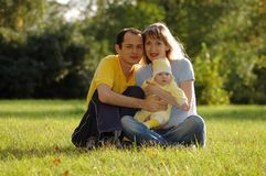 Happy family in park. Father, mother and child in park Royalty Free Stock Image