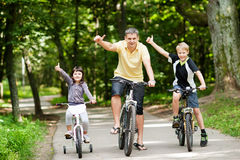 Happy family in the park on bicycles Stock Photo
