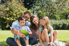 Happy family in a park with father and son inspecting leaf with Royalty Free Stock Photos