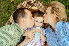 Happy family in the park on the grass. Mother and father kissing hugging their son lying on grass in nature in summer royalty free stock photos